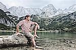 Man dangling feet in lake