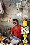Man selling garlands on city street