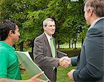Businessmen shaking hands in park