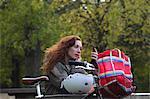 Woman applying makeup in park