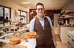 Cashier holding fruit cake in bakery