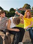Girl putting grass on boy's head