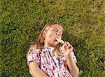 Girl enjoying ice lolly on lawn
