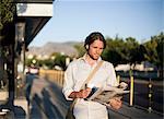 Man reading newspaper at railway station