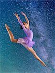 Ballerina leaping against starry night sky