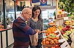 Female customer with shopkeeper in market