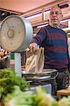 Shopkeeper weighing fresh produce in market
