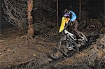 Male mountain biker riding through trees