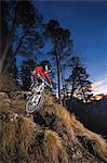 Female mountain biker riding down steep mountain track