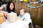 Mother handing birthday gift to baby boy