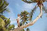 Low angle portrait of girl on palm tree, Rawa Island Malaysia