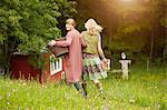 Two women in field carrying basket