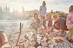 Family sitting around campfire preparing food