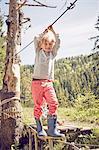 Young boy walking across single rope bridge