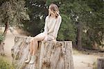 Woman sitting on tree trunk in park, Stoney Point, Topanga Canyon, Chatsworth, Los Angeles, California, USA
