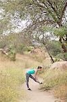 Jogger stretching in park, Stoney Point, Topanga Canyon, Chatsworth, Los Angeles, California, USA
