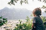 Rear view of boy looking at view of mountain range, Bludenz, Vorarlberg, Austria