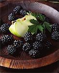 Fresh green apple slice and blackberries in wooden bowl