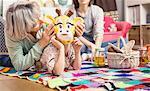 Girl wearing giraffe mask playing with grandmother on floor