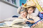 Senior woman reading to grandson wearing cowboy hat on living room floor