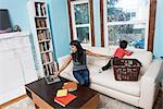 Woman using laptop while toddler son climbing on sofa