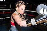 Female boxer punching boxing mitt in boxing ring