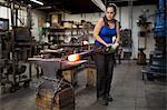 Female metalsmith turning red hot metal rod on workshop anvil