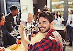 Portrait smiling, confident male bartender serving beer at bar