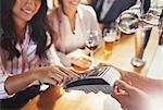 Woman paying bartender using credit card machine at bar