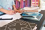 Mid section of female interior designer drawing designs at desk in retail studio