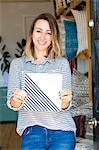 Portrait of female interior designer holding ceramic tile in retail studio