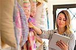 Female textile designer stocktaking cushions on retail studio shelves
