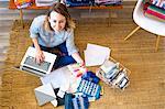 Overhead portrait of female interior designer using laptop on floor in retail studio