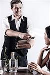 Waiter serving diner in restaurant, waiter using digital tablet