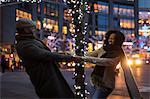 Couple holding hands around illuminated tree at night, New York, USA