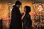 Romantic couple handing christmas gifts at night, New York, USA