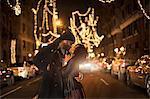 Romantic couple kissing by Christmas lights at night, New York, USA