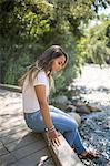 Teenage girl sitting on footbridge gazing at river