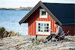 Woman reading book at coast