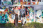 Full length of girls holding skateboards while standing against graffiti wall