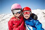 Cheerful siblings in ski-wear standing against snowcapped mountain