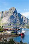 Ship in the blue sea frames the fishing village and the rocky peaks, Reine, Moskenesoya, Lofoten Islands, Norway, Scandinavia, Europe