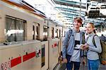 Caucasian tourist couple at train station, Tokyo, Japan