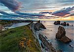Sunset Arnia Beach (Spain, Atlantic Ocean) coastline landscape.