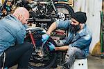 Two mature men, working on motorcycle in garage
