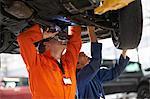 College mechanic students inspecting underneath car in repair garage