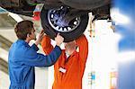 College mechanic students inspecting car wheel in repair garage