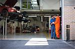 College mechanic students reading manual in repair garage