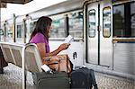 Mature woman waiting on train platform reading guidebook