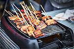 Pork belly sticks in a street kitchen